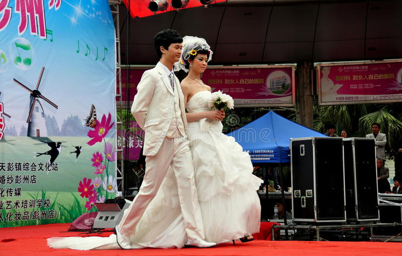 Pengzhou, China: Models on Fashion Runway. Model with her escort walking the runway in a traditional white wedding gown at the Venus Wedding Plaza fashion show stock photos
