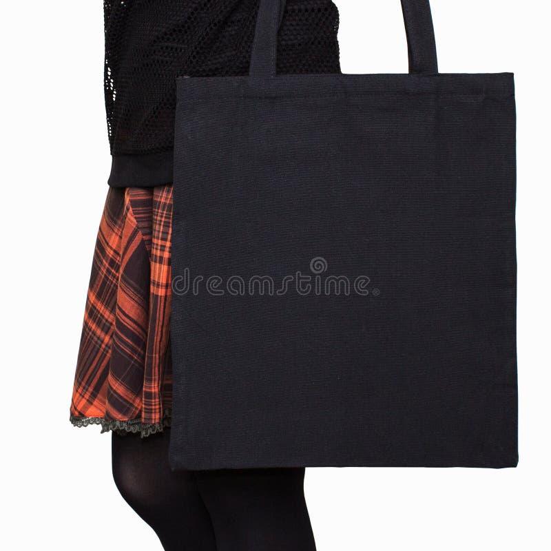 Model Het meisje in oranje rok houdt zwarte katoenen totalisatorzak Met de hand gemaakte eco het winkelen zak voor meisjes Hallow royalty-vrije stock foto