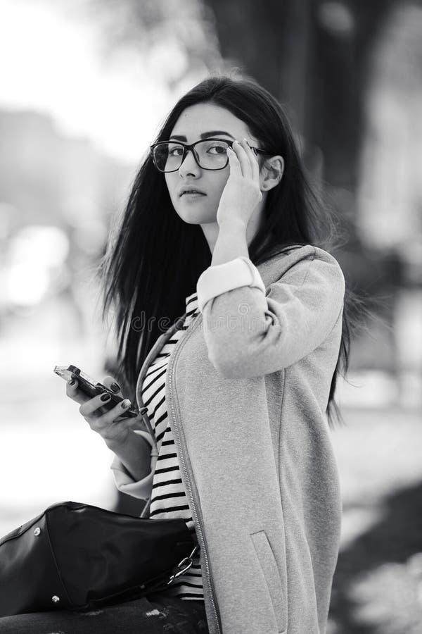 Model in het midden van stad met telefoon stock afbeelding