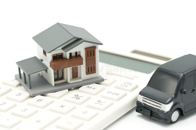 A model house model and car model is placed on a calculator. as background property real estate concept with copy space royalty free stock image