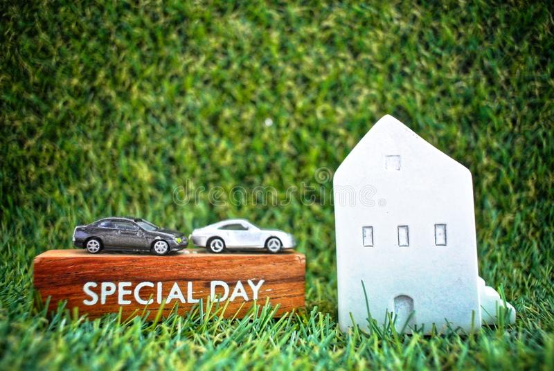 Model house, cars and a wooden box labeled Special Day on the grass background.Finance and Home Loan Concept. The message on the plank written as Special day royalty free stock photography