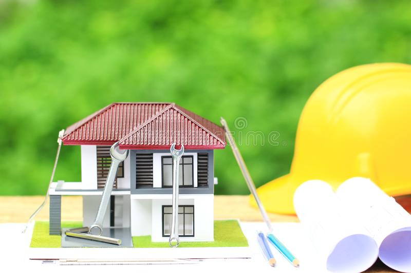 Model house and construction tools with Yellow helmets and architect rolls plans on natural green background, Repair maintenance stock image