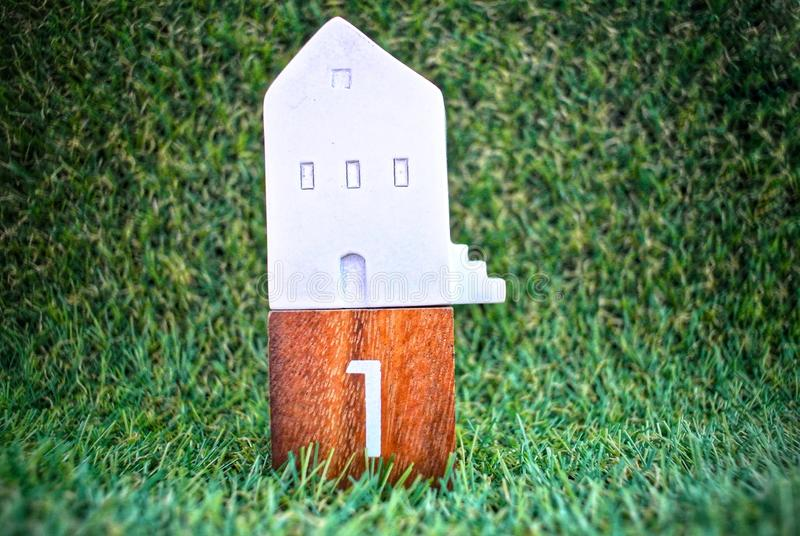 Model house  on the grass background.Finance and Home Loan Concept. Model house on wooden block no. 1, model car on wooden block no. 2 On the grass background stock images
