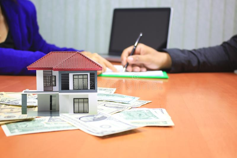 Model house on money and Businessman signing documents on the table, New home and real estate concept.  royalty free stock image