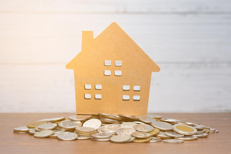 Model house put on many stack of coin on wooden table royalty free stock photos