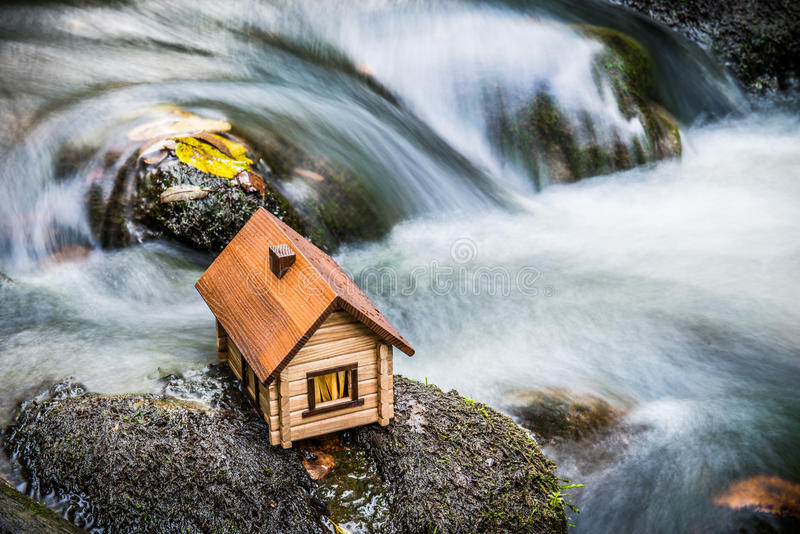 Model house beside rushing water. Small model wooden house with pitched roof and chimney placed on rocks beside water in rapidly flowing river royalty free stock photography