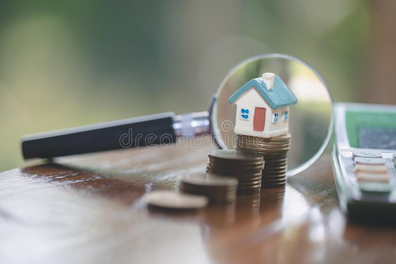 Model house on stack coin , magnifying glass searching for a new home, House searching concept with a magnifying glass royalty free stock photos