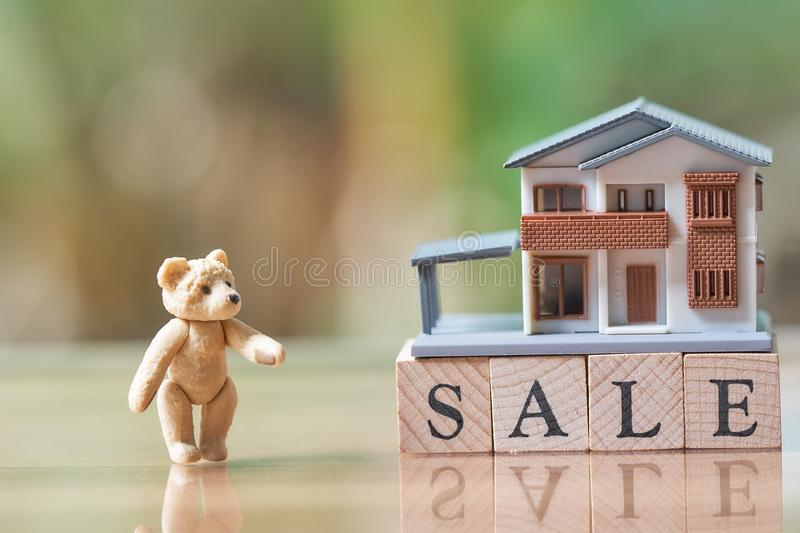 A model house model and Teddy Bear is placed on wood word sale.as background business concept and real estate concept. With copy space stock photo