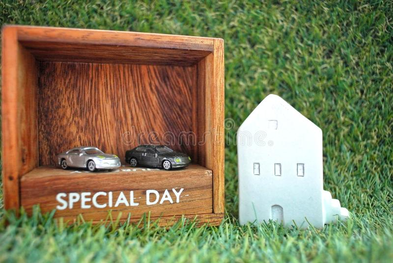 Model house, cars and a wooden box labeled Special Day on the grass background.Finance and Home Loan Concept. Model house on wooden block no. 1, model car on stock photos