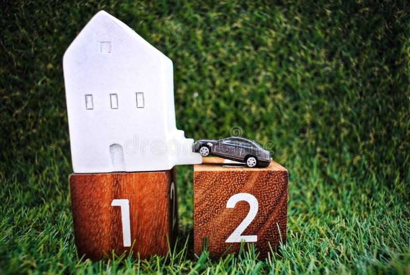 Model house on wooden block no. 1, model car on wooden block no. 2 On the grass background. financial concept. Car model on wooden number 1 on the grass royalty free stock photography
