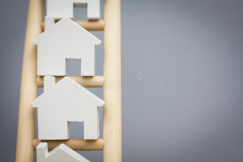 Model Houses On Rungs Of Wooden Property Ladder royalty free stock photos