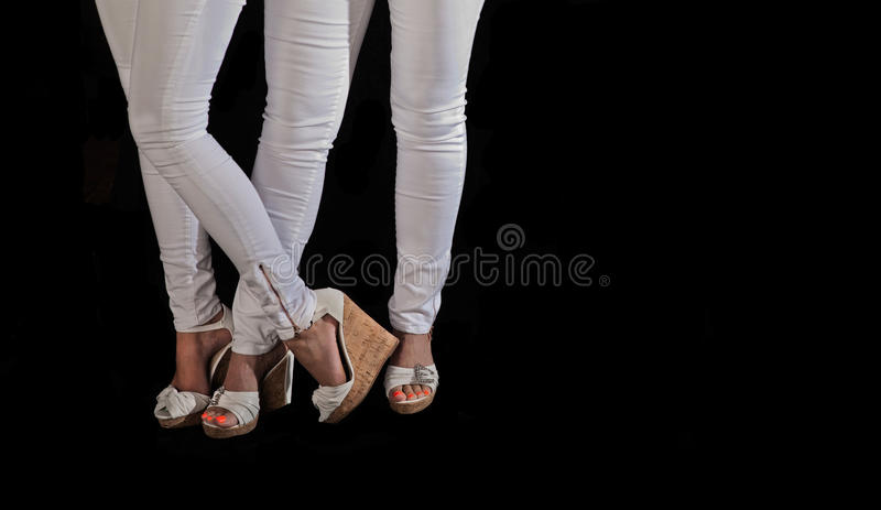 Model legs, high heels and white tight pants. Models with white stretch denim pants and high cork heel shoes with black background standing next to each other royalty free stock photo