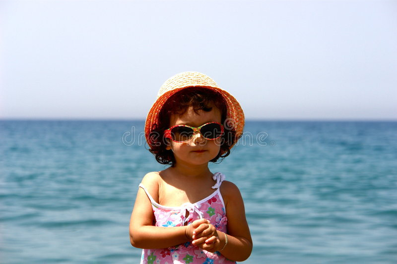 Model little girl. With sunglasses on the beach royalty free stock image