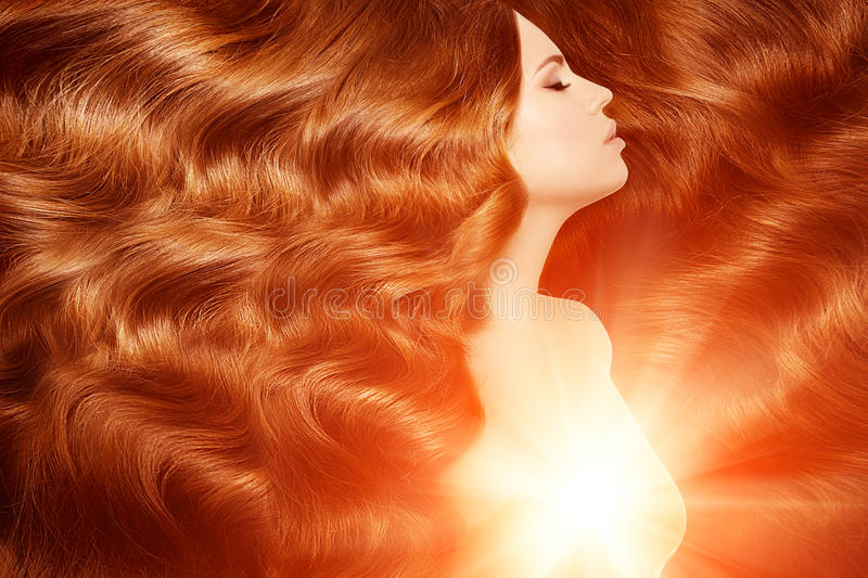 Model with long red hair. Waves Curls Hairstyle. Hair Salon. Updo. Fashion model with shiny hair. Woman with healthy hair girl wi royalty free stock images