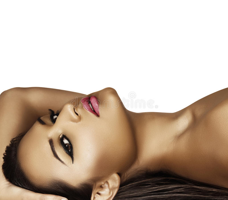 Model lying with fashion make-up. Beautiful latin model with tan with fresh summer fashion make-up and dark liner on her eyes lying on her long wet hair stock photos