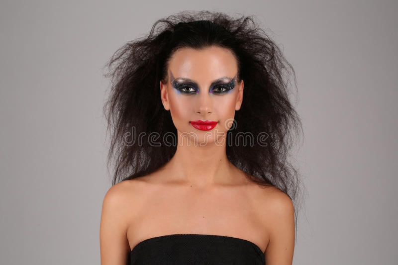Model with makeup and wild hair. Close up. Gray background stock images