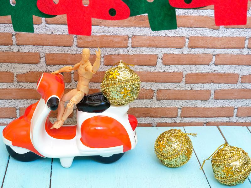 a model man on a motorcycle and three gold Christmas balls stock photos