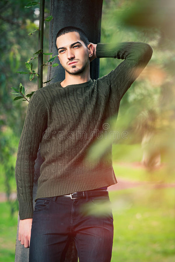 Model man short hair leaning against a tree in a nature scene stock photography