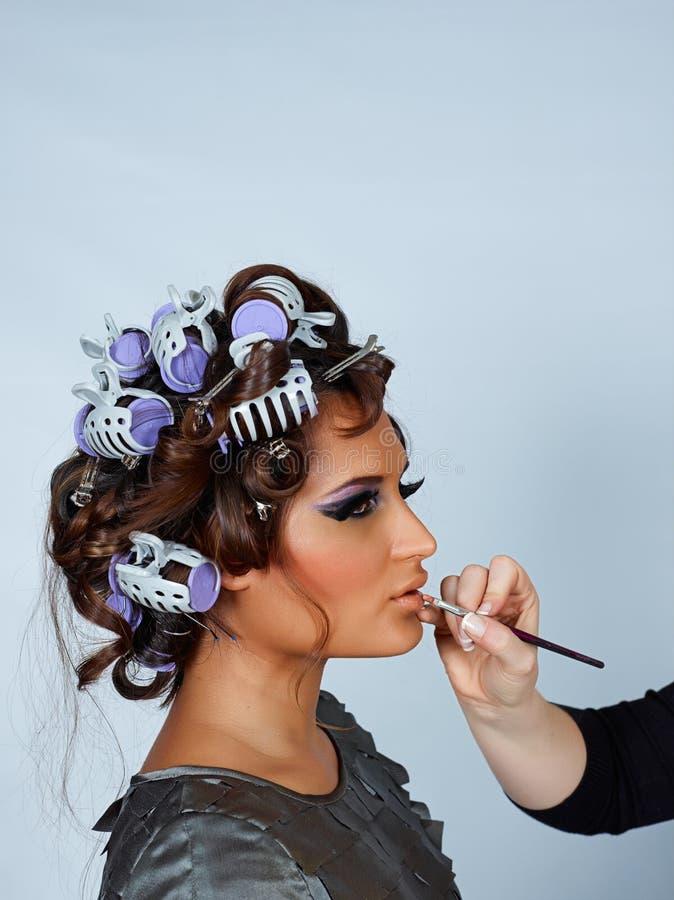 Model met haar in krulspelden en lippenstiftborstel. royalty-vrije stock foto's