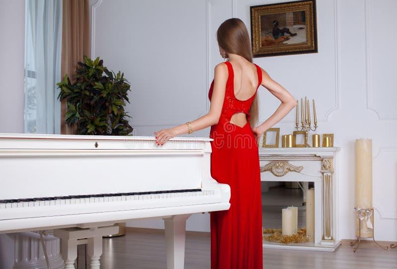 Model met het mooie lange haar stellen in rode kleding stock foto