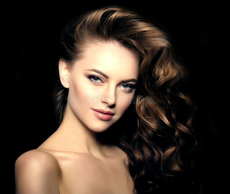 Model met lang haar op een zwarte achtergrond Golvenkrullen Hairstyl stock foto