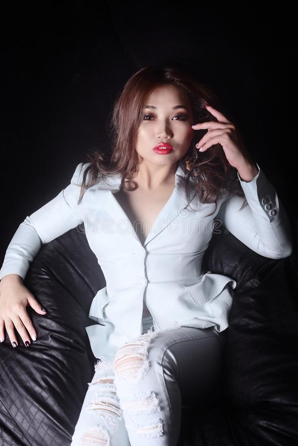 Model met make-up in een elegant kostuum en gescheurde jeans als zwarte voorzitter op een zwarte achtergrond royalty-vrije stock afbeelding