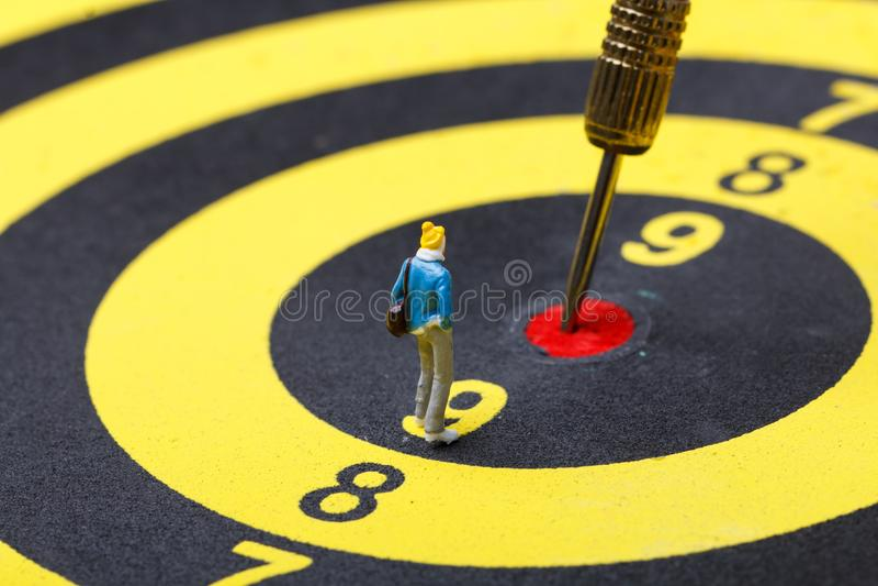 Model mini people walks towards the target on dart board. stock images