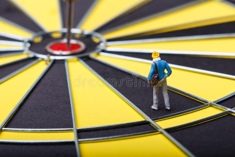 Model mini people walks towards the target on dart board. stock photo