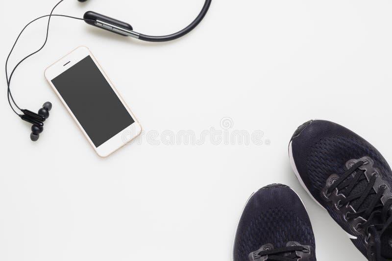Model mobiele cellphone met draadloze bluetoothoortelefoon en loopschoenen op witte achtergrond Gezonde actieve levensstijlen royalty-vrije stock afbeelding