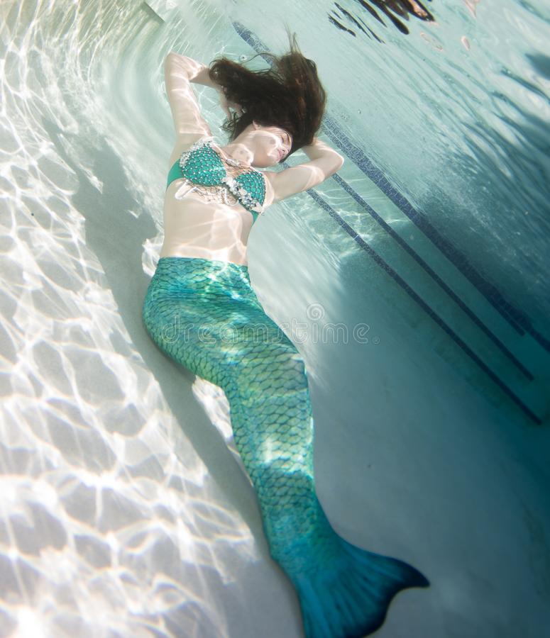 Model onderwater in een pool die een meerminnenstaart dragen stock foto's