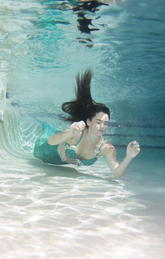 Model onderwater in een pool die een meerminnenstaart dragen stock afbeeldingen