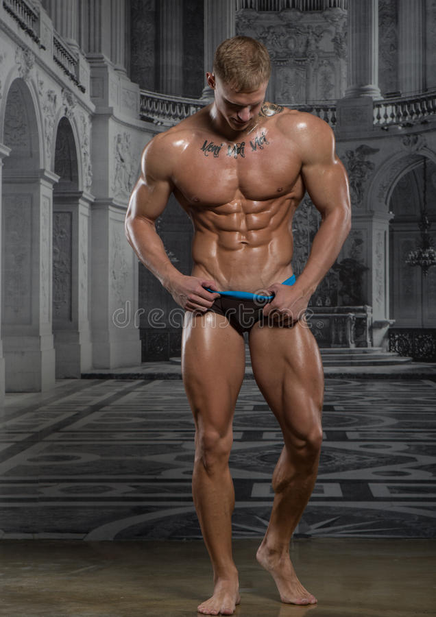 Model in palace. Muscled male model posing on palace wallpaper background stock image