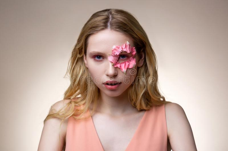 Model with pink eyeshades having flower petals around eye. Pink eyeshades. Model with blonde wavy hair and pink eyeshades having flower petals around eye stock photography