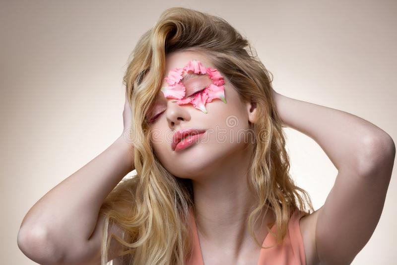 Model with pink eyeshades and petals near eye showing poses. Real tenderness. Tender model with pink eyeshades and little pink petals near eye showing poses stock photo