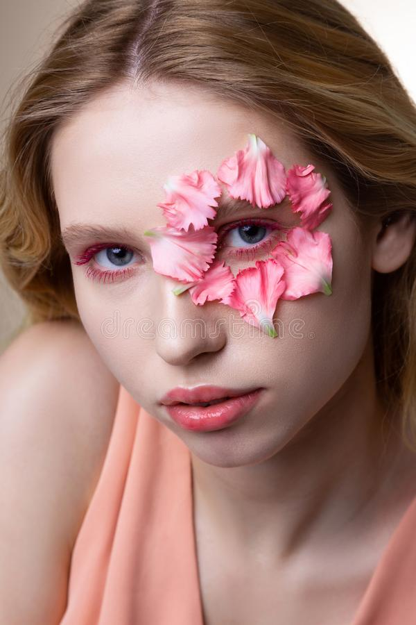 Model with pink eyeshades showing little pink petals on face. Showing petals. Blue-eyed model with pink eyeshades showing little pink petals on face while posing royalty free stock image
