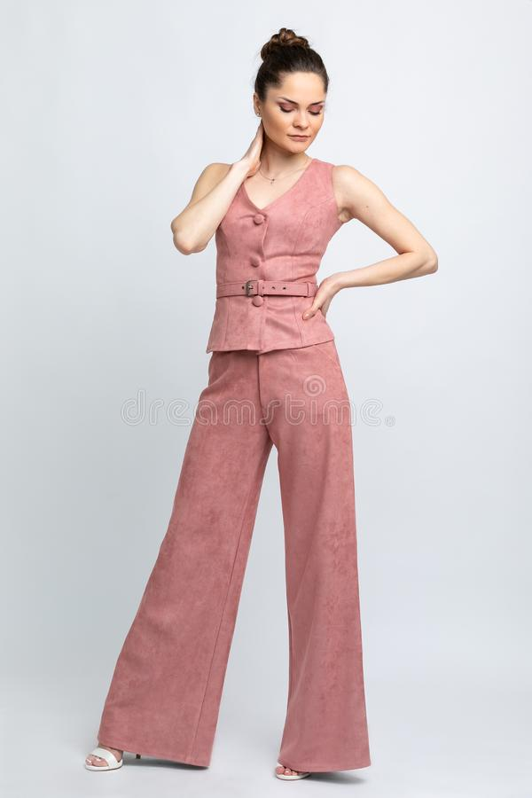 Model in pink waistcoat with belt and in pink trousers flared, in white sandals with heels, with silver chain around neck, isolate. D on white backdrop of royalty free stock image