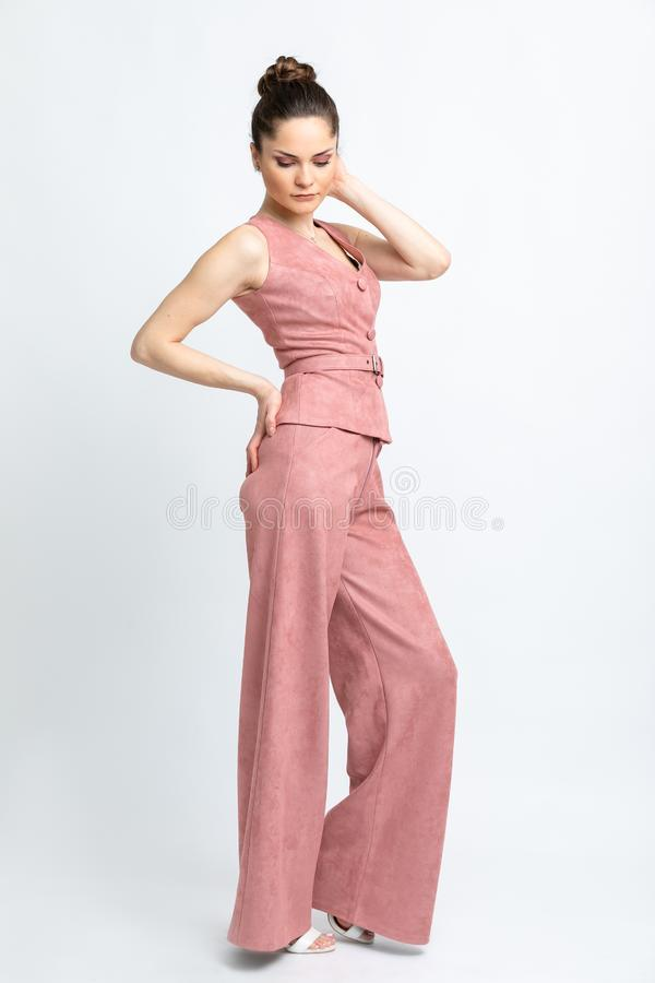 Model in pink waistcoat with belt and in pink trousers flared, in white sandals with heels, with silver chain around neck, isolate. D on white backdrop of stock photos