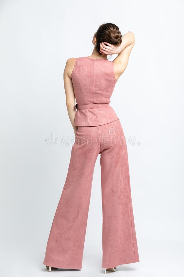 Model in pink waistcoat with belt and in pink trousers flared, in white sandals with heels, with silver chain around neck, isolate. D on white backdrop of royalty free stock photography