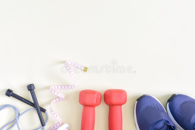 A model with a place for text on a sports theme. Fitness background. Dumbbells, skipping rope, sneakers are located on a. Light background. Photo from the top royalty free stock photos