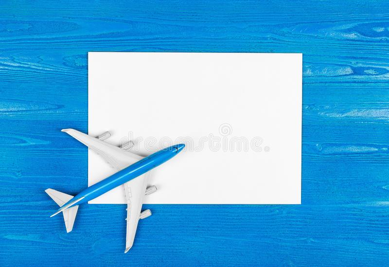 Model of airplane and blank sheet of paper on the blue wooden background. Travel concept. stock photo