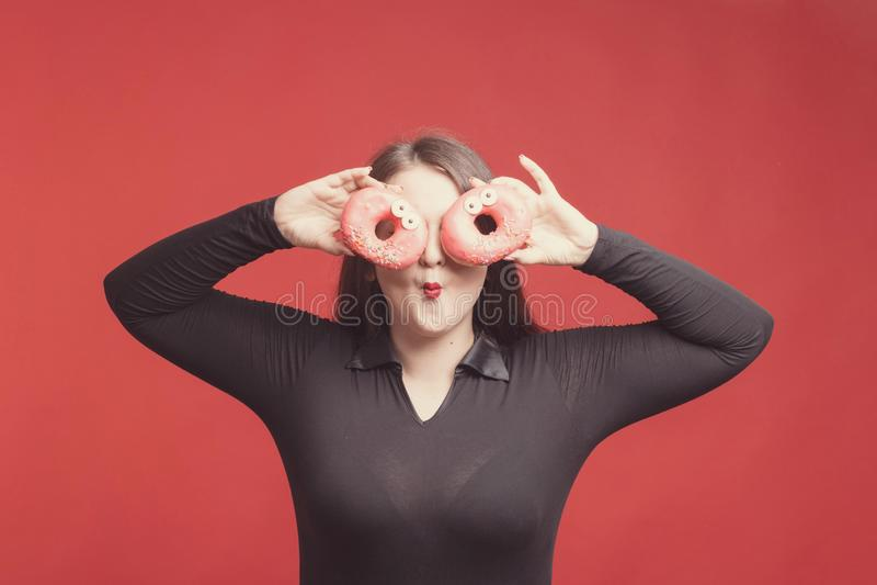 Model plus grootte met zoete donuts, gelukkige meisjes glimlachende holding in handencakes die haar ogen, in zwarte bodysuit beha stock fotografie