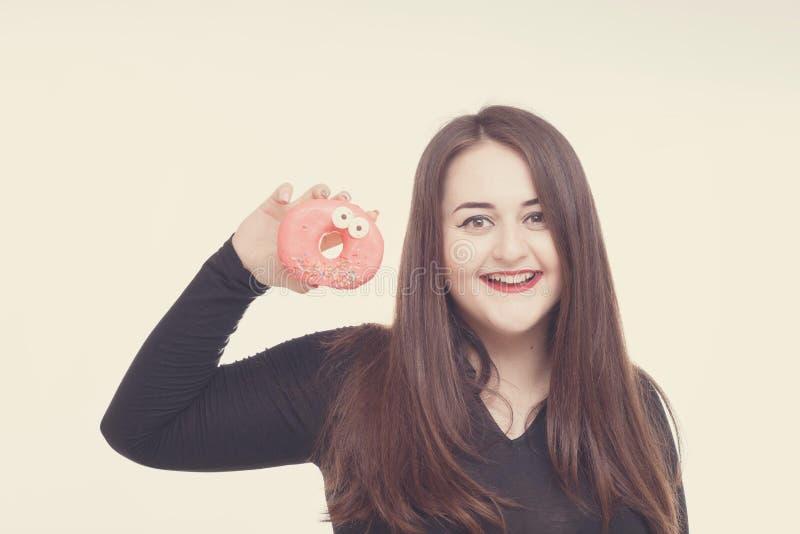 Model plus grootte met zoete doughnut, gelukkige meisjes glimlachende holding in handen donuts, in zwarte bodysuit XXL-wijfje op  stock foto's