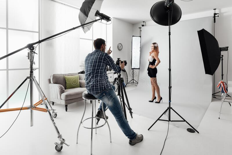 Model posing for a photo shoot. Young beautiful female model posing for a photo shoot in a studio, a photographer is shooting with a digital camera royalty free stock photography