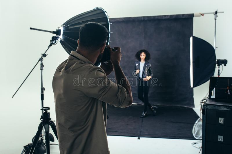 Photographer doing a photo shoot in a studio. Model posing for a photograph during a photo shoot. Studio shot of a photographer shooting photos of a women with stock image
