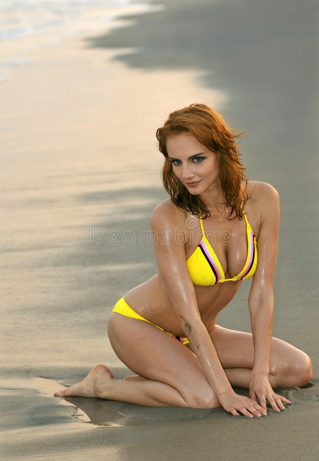 Model posing pretty at rocky beach in swimsuit stock image