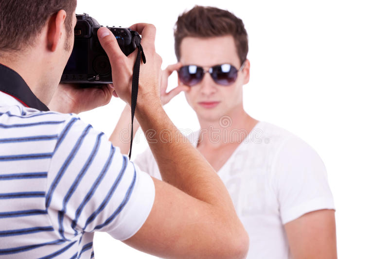 Model posing for a professional photographer. Young male fashion model posing for a professional photographer on white background. young men wearing sunglasses stock images