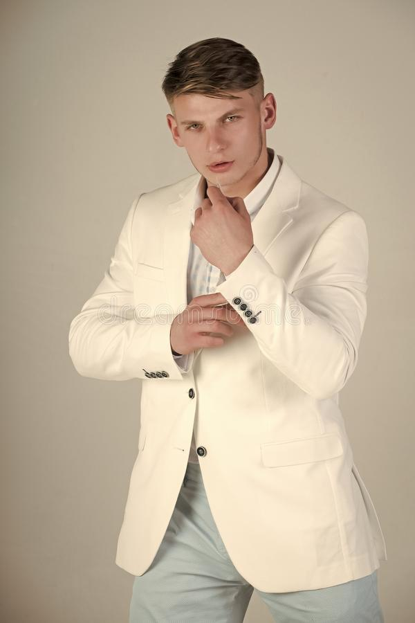 Model posing in white jacket, striped shirt and blue pants royalty free stock image