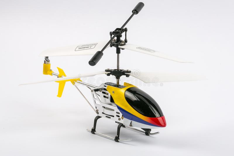 Model radio-controlled helicopter with remote control. Made of metal body, with plastic blades, yellow, blue and red color,isolate stock photo