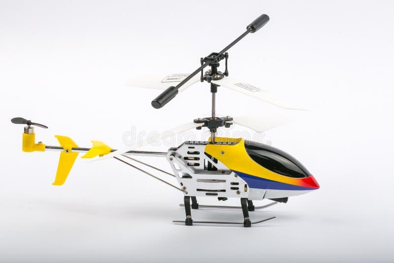 Model radio-gecontroleerde helikopter met afstandsbediening Gemaakt van metaallichaam, met plastic bladen, isoleert de gele, blau royalty-vrije stock afbeeldingen