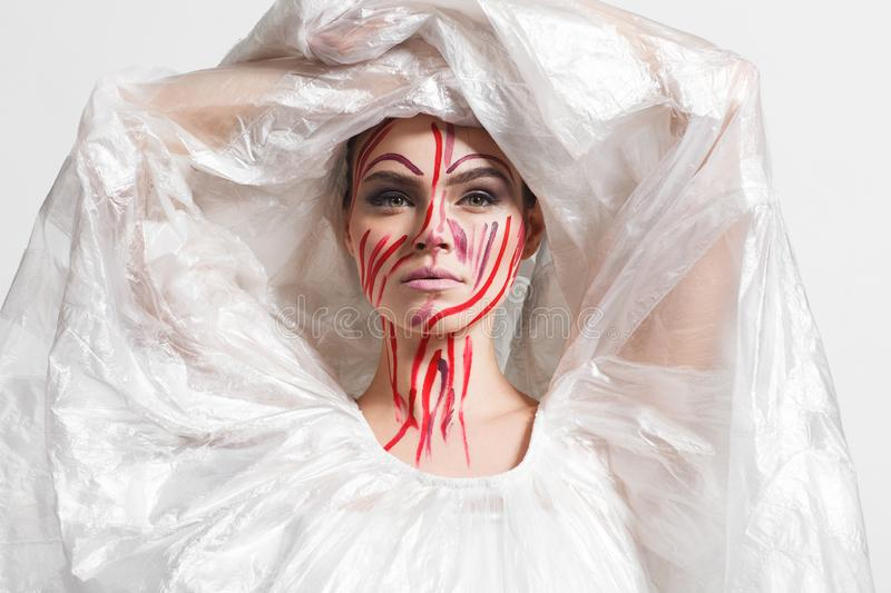 Model in a raincoat made of cellophane and in creative make-up. Studio photo session. White background stock photo